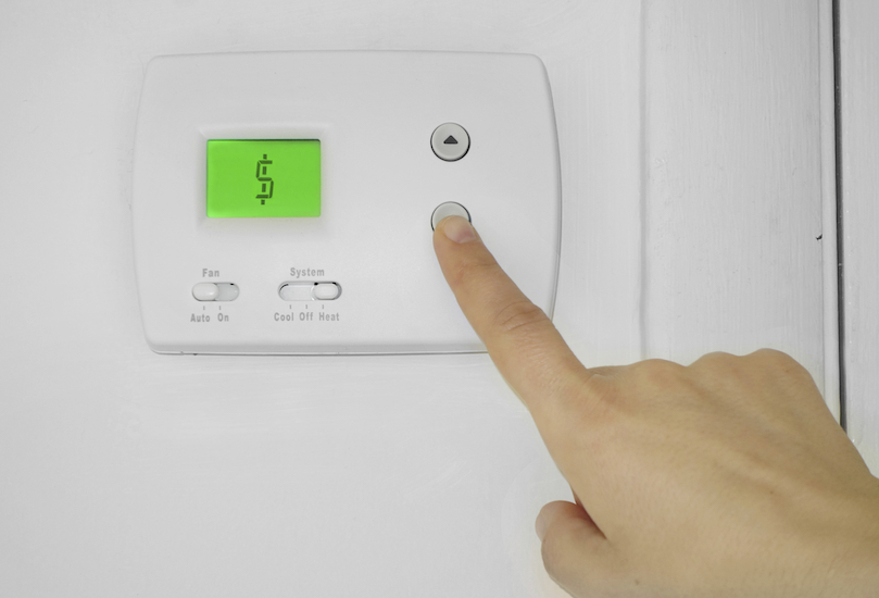 thermostat displaying dollar sign while person pushes the down button